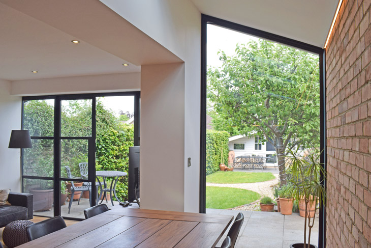 French doors connect the outdoors to the indoors and a picture window frames the garden view.