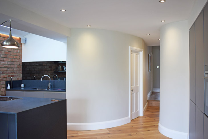 The use of curved walls to connect spaces and keep the living flow.