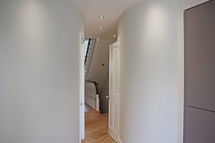 The use of curved walls to connect spaces and keep the living flow. Note the under stairs cupboard is removed to open up the space.
